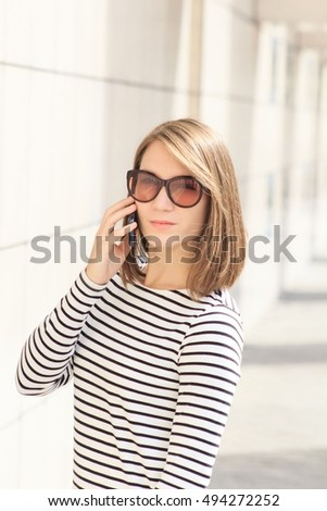 Portrait of young smiling woman talking on phone in the street