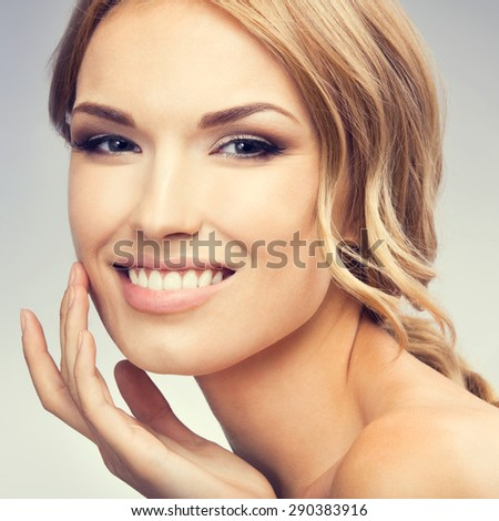 Portrait of young smiling woman touching skin or applying cream. Beauty and health concept. - stock photo