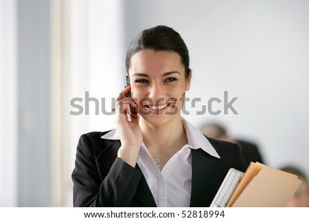 Portrait of young smiling woman with cell phone and documents - stock photo