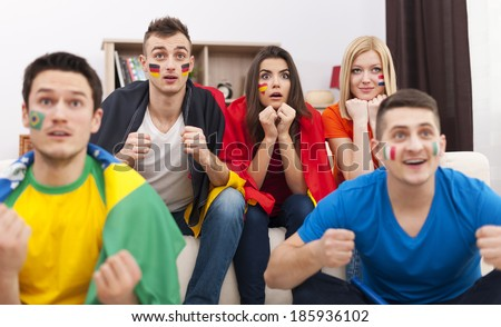 Portrait of young soccer fans during the watching match on TV  - stock photo