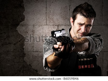portrait of young soldier aiming with gun against a grunge bricks wall