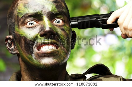 portrait of young soldier comitting suicide against a nature background - stock photo