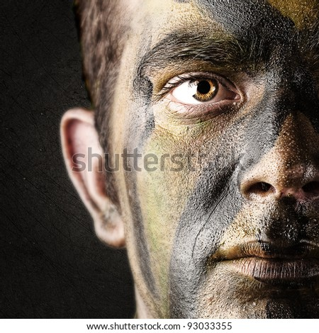 portrait of young soldier face against black background - stock photo