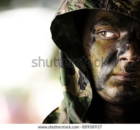 portrait of young soldier face with hood over abstract background - stock photo