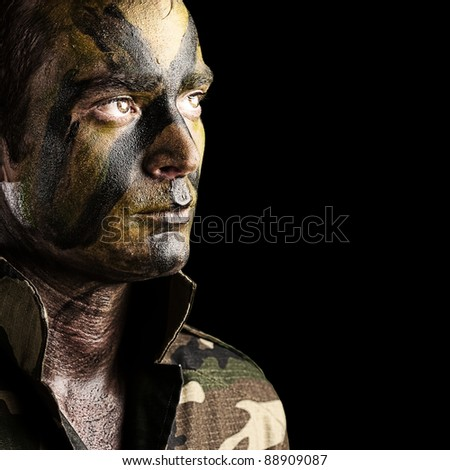 portrait of young soldier face with jungle camouflage against a black background - stock photo
