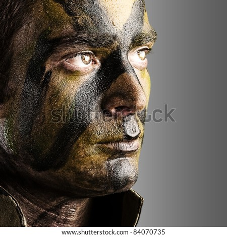 portrait of young soldier face with jungle camouflage paint against a white background - stock photo