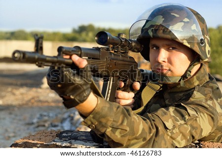 Portrait of young soldier in camouflage with machine gun - stock photo