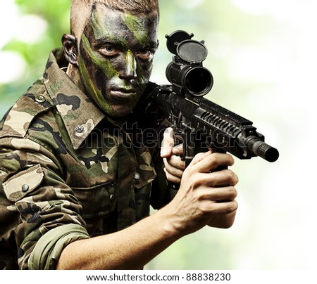 portrait of young soldier pointing with rifle in the jungle - stock photo