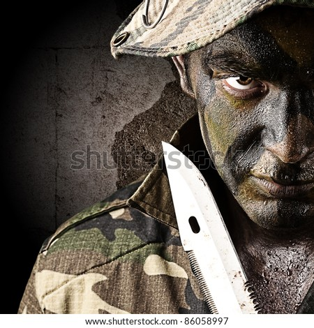 portrait of young soldier trying to suicide against a grunge wall - stock photo