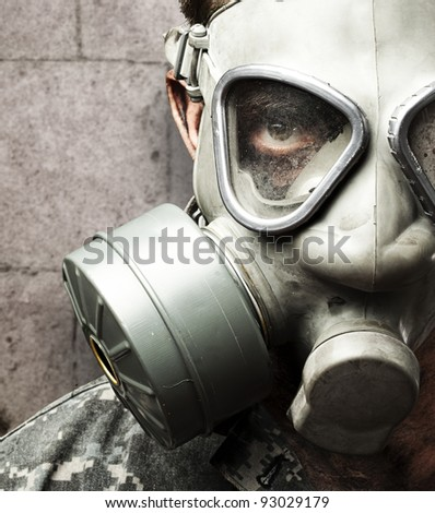 portrait of young soldier wearing gas mask against a grunge bricks wall - stock photo