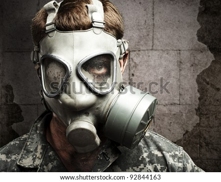 portrait of young soldier wearing gas mask against a vintage wall