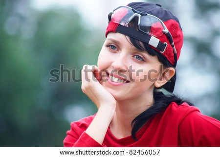 Portrait of young sports woman in red t-shirt and cap on summer background
