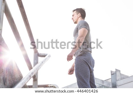 portrait of young sportsman stopped to rest near the iron fence after intensive jogging, man resting after workout outdoors - stock photo