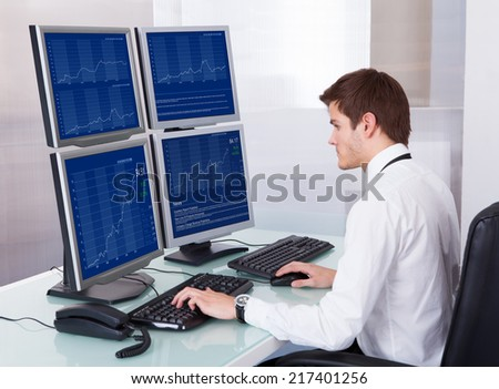 Portrait Of Young Stock Broker Using Computer At Desk - stock photo