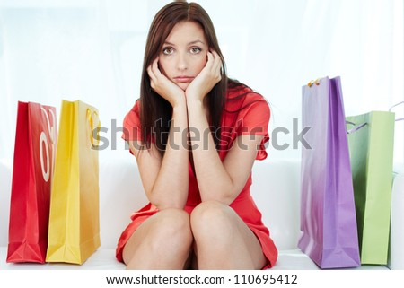 Portrait of young stressed brunette surrounded by paperbags - stock photo