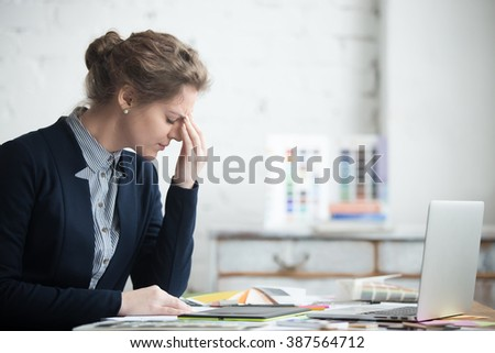 Portrait of young stressed woman sitting at home office desk in front of laptop, touching head with tired facial expression, having headache, low or high arterial blood pressure, stress - stock photo