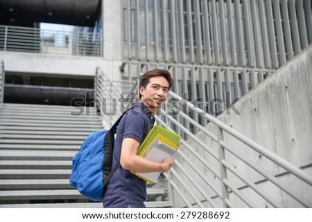 portrait of young student holding book with bag at campus - stock photo