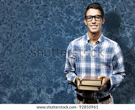 portrait of young student with glasses against a vintage wall - stock photo