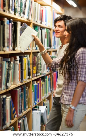 Portrait of young students choosing a book in a library - stock photo