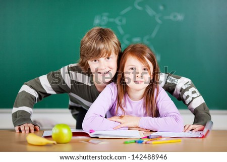 Portrait of young students looking at the camera over the blackboard background
