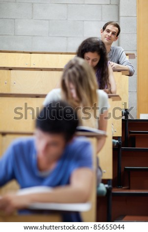 Portrait of young students writing in an amphitheater with the camera focus on the background - stock photo