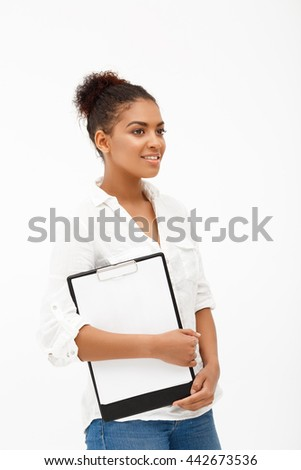 Portrait of young successful african business lady holding folder, smiling over white background.