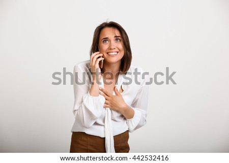 Portrait of young successful business woman speaking on phone, smiling over white background.