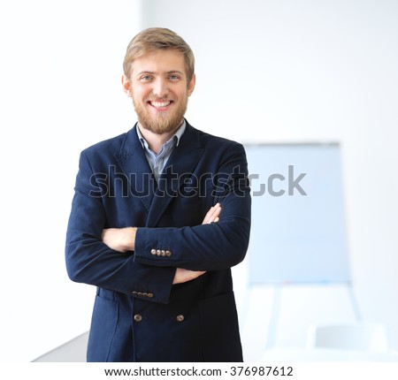 Portrait of young successful businessman in the office. Crossed arms - stock photo