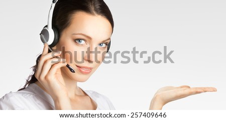 Portrait of young support phone operator in headset showing something or blank copyspace area for text or slogan, over grey - stock photo