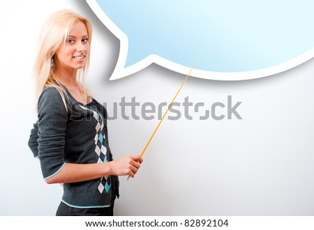 Portrait of young teacher pointing on white marker board in modern educational room. Blank balloon with copyspace for your text and logo. - stock photo