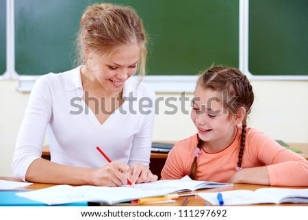 Portrait of young teacher showing her pupil how to draw at lesson - stock photo