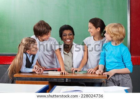 Portrait of young teacher sitting at desk with students looking at her in classroom - stock photo