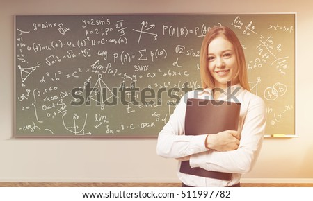 Portrait of young teacher standing in a classroom with formulas on green blackboard. Concept of education. Toned image