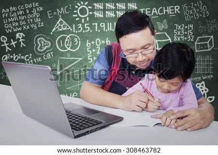 Portrait of young teacher teach his female student to write on the book, shot in the classroom - stock photo