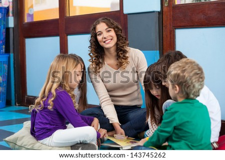 Portrait of young teacher with children reading book while sitting on floor in classroom - stock photo