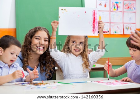 Portrait of young teacher with girl showing drawing while students painting at desk - stock photo