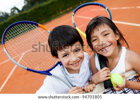 Portrait of young tennis players smiling at the court - stock photo
