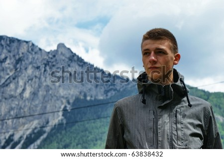 Portrait of young tourist with mountains in background