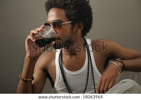 Portrait of young trendy african man drinking from a glass - stock photo