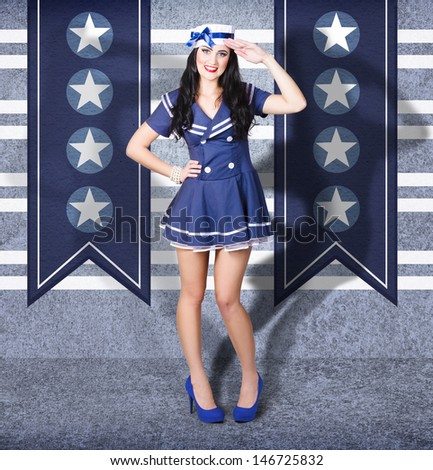 Portrait of young US marine corps pin-up girl with brunette hair and bright makeup saluting in navy style while dressed as a sailor.  - stock photo