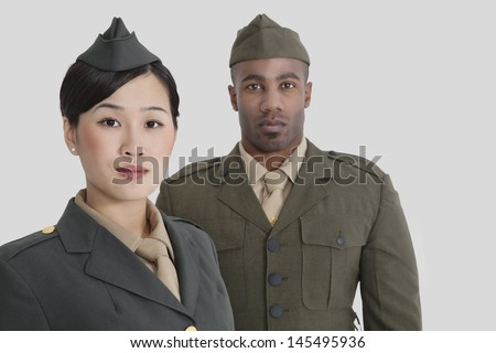 Portrait of young US military officers in uniform over gray background - stock photo
