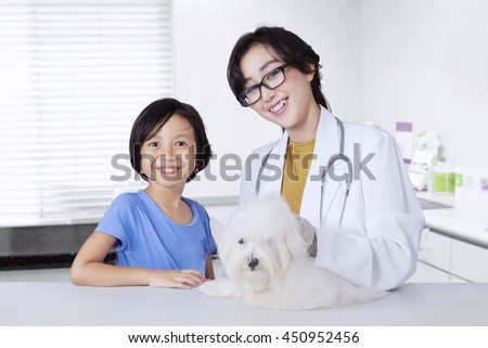 Portrait of young veterinarian and little girl smiling at camera with a dog on the desk in the clinic - stock photo