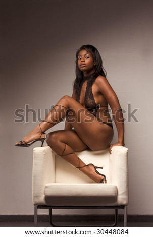 Portrait of young voluptuous sensual Hispanic woman in brown lingerie sitting on top of armchair - stock photo