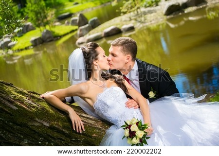 portrait of young wedding couple in park, beautiful bride with groom , summer nature outdoor - stock photo
