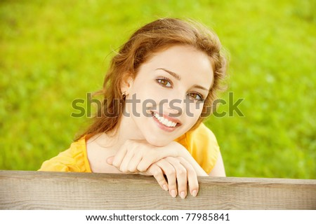 Portrait of young woman against green summer grass. - stock photo