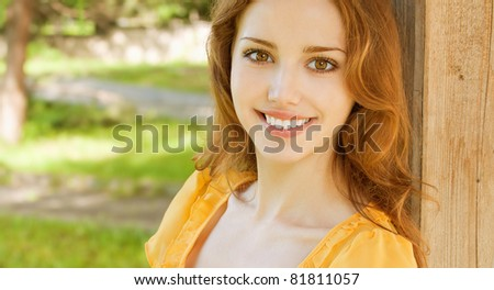 Portrait of young woman against green summer grass.
