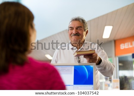Portrait of young woman and happy old retired man returning book to library - stock photo