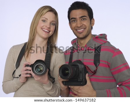 Portrait of young woman and man with digital cameras in studio - stock photo