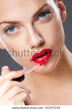Portrait of young woman applying lip gloss - stock photo
