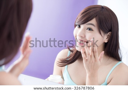 Portrait of young woman applying moisturizer cream on her pretty face and look mirror. asian beauty - stock photo